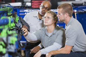 An African American man instructing Caucasian students on how to repair a diesel engine. He is teaching a class in a vocational school, for learning the auto mechanic trade. They are kneeling by an engine block which is color-coded for the classroom. The focus is on the young woman in the middle.