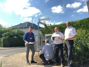Bei der Baustellenkontrolle (von links): Lukas Meudt (Projektleiter der Telekom), Michael Rieke (ateneKOM, knieend), Jan Bonkewitz (ateneKOM) und Martin Rudersdorf am Glasfasernetzverteiler vor der Grundschule Beselich.
